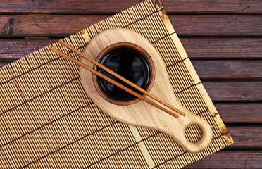 Bamboo mat, soy sauce, chopsticks on dark wooden table. Top view with copy space