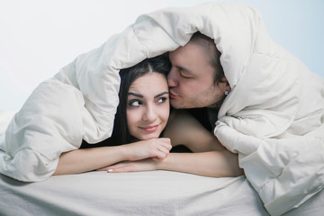 beautiful couple in bed lying under a white blanket, the brunette looks at the guy, he's kissing a girl