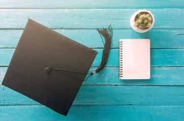 graduation cap, hat on blue wood table with Empty notebook view from above.