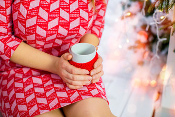 girl in red dress is holding a cup of coffee, closeup. On the background of a New Year tree