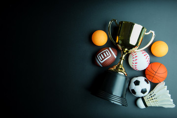 Golden trophy, Football toy, Baseball toy, Ping pong ball, Shuttlecock, Basketball toy and Rugby toy isolated on black background with copy space.Concept winner of the sport.