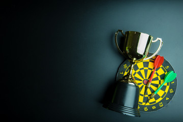 Golden trophy, Darts with crotch isolated on black background with copy space.Concept winner.