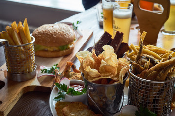 set of appetizers: roast pork knuckle with garlic and onion rings in batter, fried slices of potatoes, cabbage, pickles and various sauces - mustard and mayonnaise with herbs