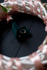 Wedding ring in jewelry box with white summer wreath with flowers on black background