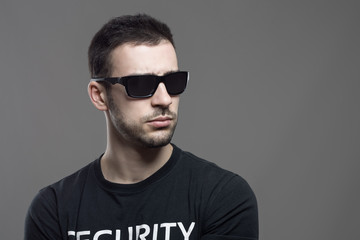 Macho tough security agent wearing sunglasses looking away at copyspace. Atmospheric contrasty portrait over gray studio background.
