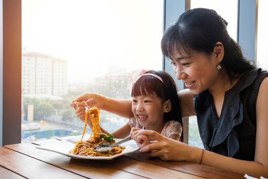 Asian Chinese mother and daughter eating spaghetti bolognese