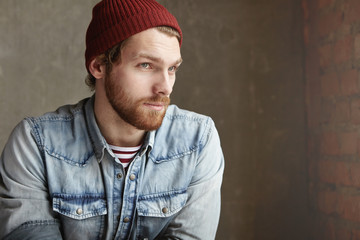 Half profile of handsome hipster with beard dressed in trendy clothing having thoughtful look waiting for someone at cafe, sitting against concrete wall background with copy space for your information