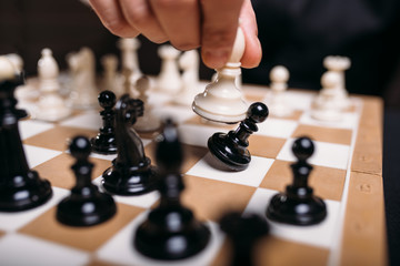 Male chess player hand holding white figure