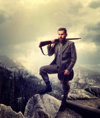 Bearded old-fashioned hunter in rocky mountain