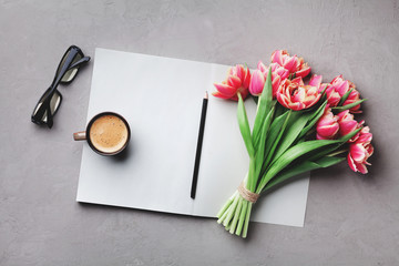 Coffee, clean notebook, eyeglasses and beautiful flower on stone table top view in flat lay style. Woman working desk with cozy breakfast.