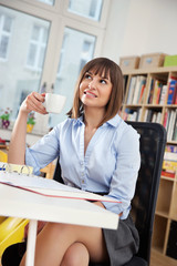 Beautiful young Woman in her Cozy Home Office at work, having a little Coffee Break