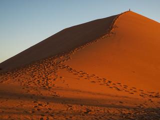Sand dune ridge to summit with footprint in vast desert
