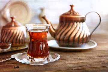 Turkish tea in traditional glass on wooden table closeup