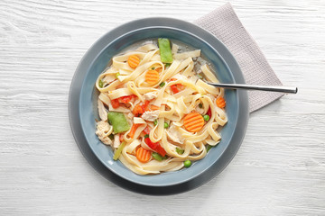 Chicken noodle soup in plate on wooden background