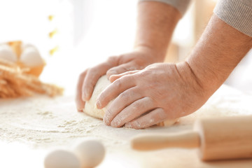 Hands of man making dough in kitchen