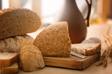 Wooden board with cut bread on kitchen table