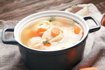 Ceramic pan with delicious chicken and dumplings on decorative napkin