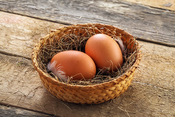 Two fresh farm eggs in a basket with hey and feather on a wooden table. Close-up shot. Top view.