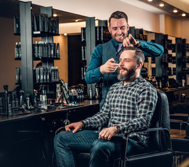 Stylish male hairdresser doing haircut to a bearded male in a saloon.