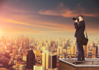 Photographer with digital camera against cityscape