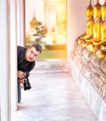 Photographer with digital camera in Buddha temple