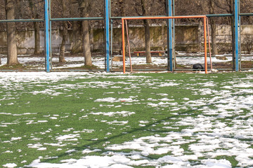 football field in the snow in spring