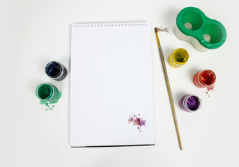 Closeup of blank spiral notepad surrounded with watercolor paint, glass of water and paintbrush. Mock up
