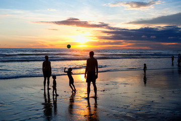 Children and adults play ball on the beach during sunset