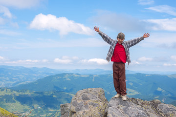 Joyful boy with open arms stands on the cliff in the mountain