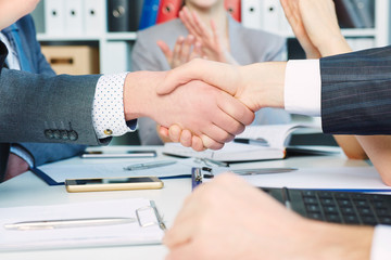 Close up businessmen handshake on team meeting with clapping group of people blured in background at modern startup business office interior.