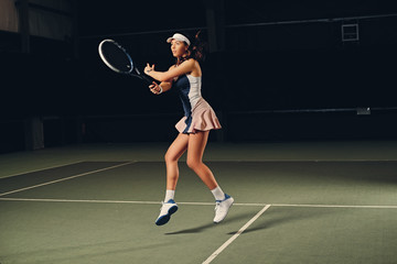 Female tennis player in action in a tennis court indoor.
