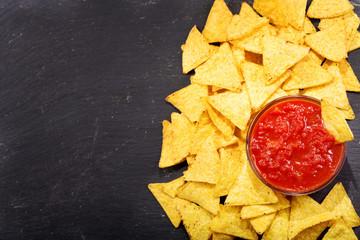 nachos with salsa on dark table