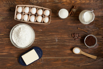 Ingredients for making cinnamon rolls on a wooden background