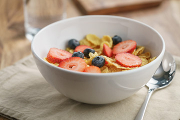 dry corn flakes with berries in bowl on table
