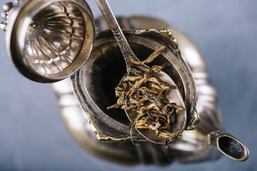 Dry green tea leaves in metal vintage spoon over open teapot