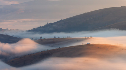 Church on the hill in foggy morning. Carpathians, Ukraine