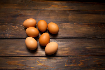Closed, fresh chicken eggs on a natural wooden background