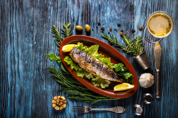 Baked mackerel with lemon on a rustic wooden background