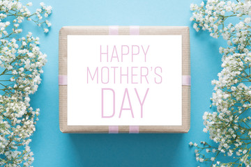 Mother's day background, blue background with white flowers and a present