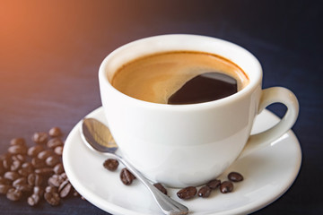 Coffee cup and beans on a dark background
