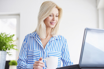 Working on new project. Shot of an attractive smiling financial businesswoman working on laptop in the office.