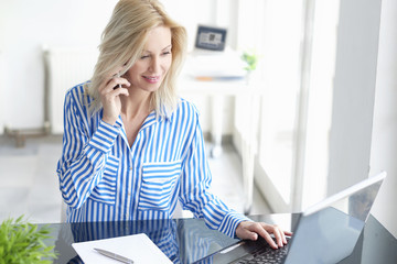 Businesswoman with mobile phone. Professional woman making a call while working on laptop at office.