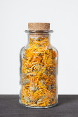 Dried marigold herb inside a glass jar. Herbs and plants for tea.