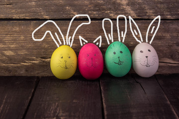 Funny bunny easter eggs on rustic wooden background