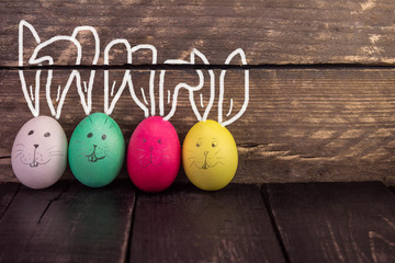 Funny cute easter eggs on rustic wooden background