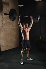 Fit young man lifting barbells looking focused, working out in a gym