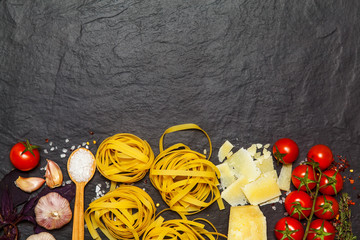 Pasta ingredients. Spaghetti with ingredients sweet basil, tomato, garlic and parmesan cheese on dark background. Top view