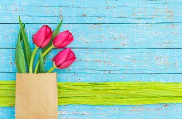 Frühlingsblumen Tulpen rot in Geschenk Tüte auf Holz Hintergrund blau
