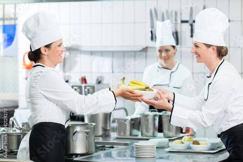 Kuchenbrigade In Einer Catering Kuche Richtet Speisen An Stockfotos
