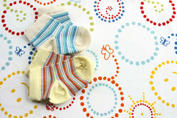two pairs of baby socks: blue and yellow striped on colorful blanket background with copy space